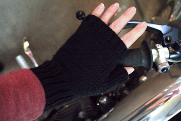 Hand knit fingerless gloves in black by motorcycle